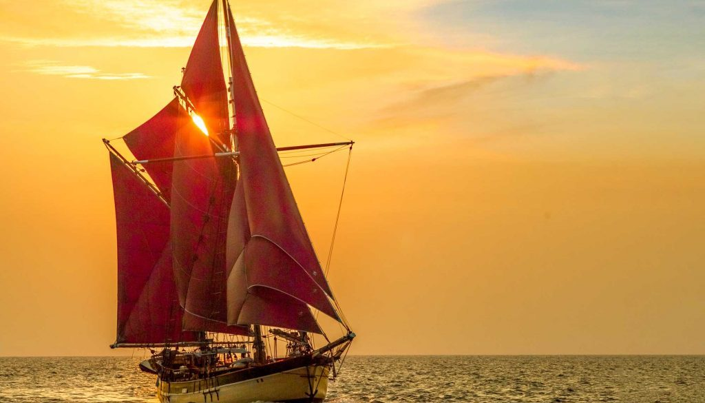 Historic Vessel Vega red sails in the sunset.