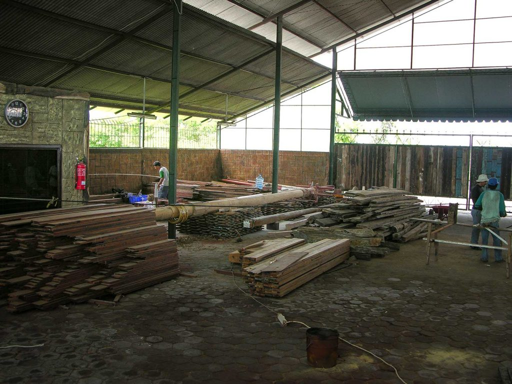 Piles of rough planks on the right become ready to work wood on the left.